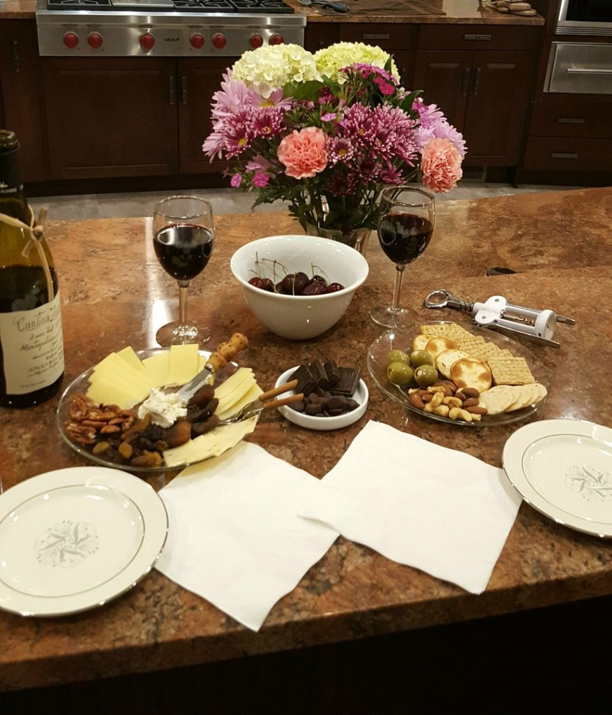Appetizer spread of cheeses, olives, mixed nuts, fresh cherries, chocolates, and crackers. These appetizers are accompanied by a bottle of red wine.