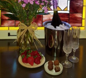 Romance package includes flowers, sparkling beverage, fruit and chocolates.